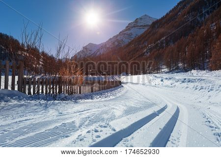 Beautiful picture of snowcapped road to alpine ski resort with snowcat tracks at sunny day