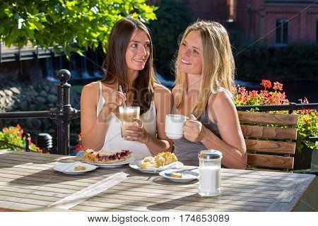 Two Beautiful Woman Friends In Outdoor Cafe