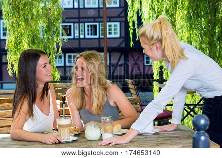 Two young women at street cafe table in European city laughing while talking to female waiter standing and looking at them