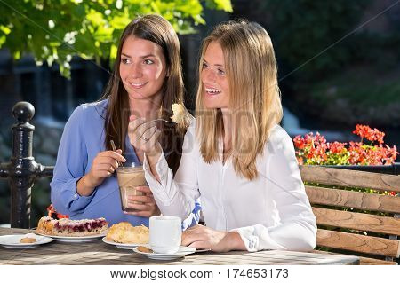 Two Women Eating In Outdoor Cafe