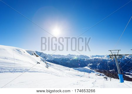 Beautiful view of mountain ski resort with ropeway and empty button lifts at sunny day