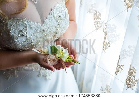 Bride holding a buttonhole. Gentle hand of the bride holding boutonniere for the groom.