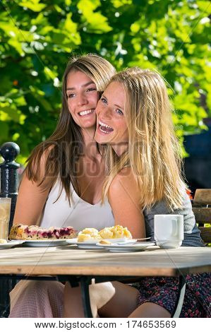 Young Women Touching Cheeks And Laughing