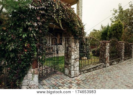 Beautiful Stone Gate With Metal Fence Near Old Victorian Stone Building Cottage Overgrown With Vines