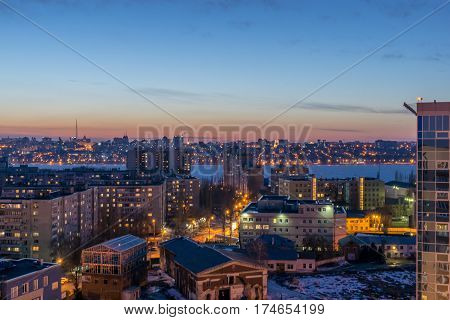 Night Voronezh city after sunset, blue hour, night lights of houses, buildings, aerial view from rooftop