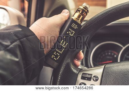 Mans hand on steering wheel of car with modern vaping device or vaporizer, or vape mod, or e-cig gadget
