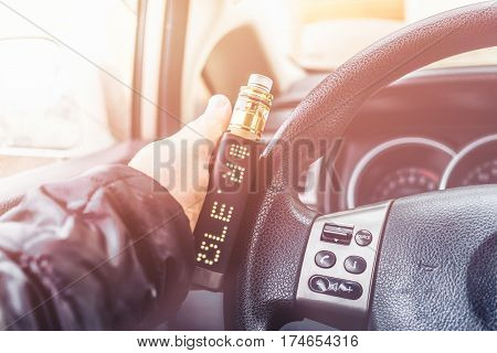 Mans hand on steering wheel of car with modern vaping device or vaporizer, or vape mod, or e-cig gadget. Toned image