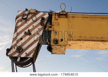 Boom truck crane against the blue sky. High-rise construction.