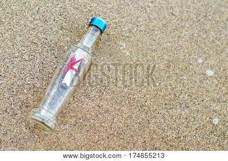 Bottle with message on the sandy beach