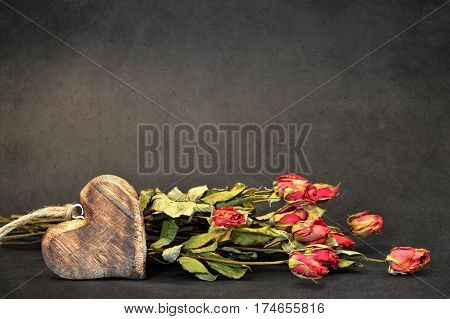 Wooden heart and wilted roses on grunge background