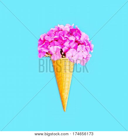 Ice Cream Cone With Flowers Over Blue Background Top View