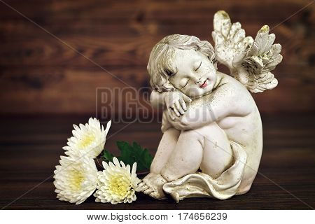 Angel figurine and white flowers on wooden background