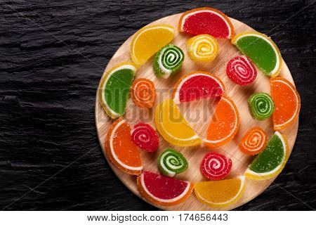 Fruit jellies. Jelly candies citrus in form lobules on a dark background. Top view.