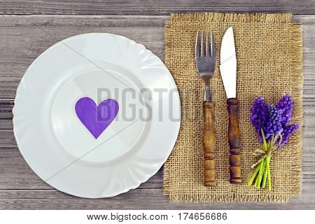 Festive spring table setting: Plate, silverware and spring flowers on wooden background