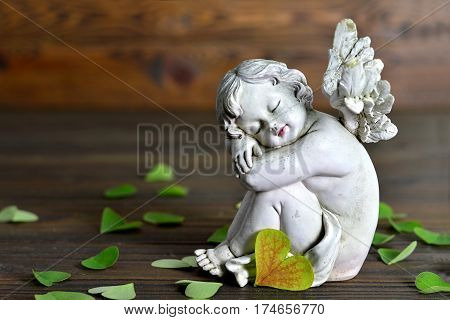 Angel and heart-shaped leaves on wooden background