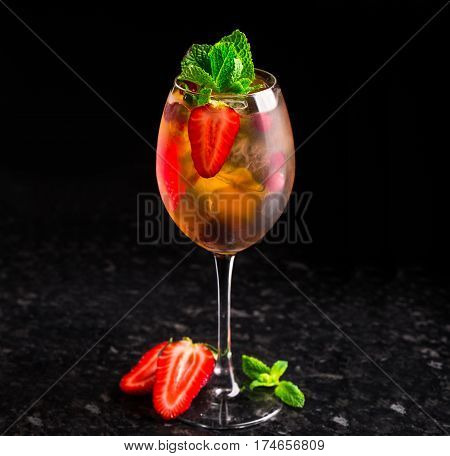 Cocktail with strawberries and mint on marble table