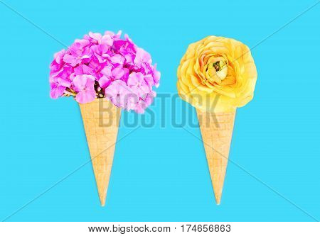 Two Ice Cream Cone With Flowers Over Blue Colorful Background Top View