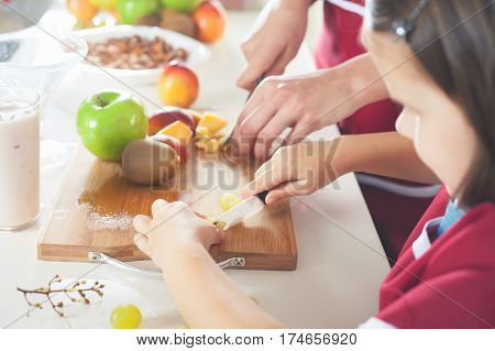 Cute little girl cooking with her mother. Healthy food, cooking healthy salad with fruits ingredients. Mom and daughter cooking together. Recipe food for baby or child