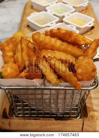 Golden French fries serving in the basket with 8 dipping sauces ketchup and mayo stylist food fusion food Close-up