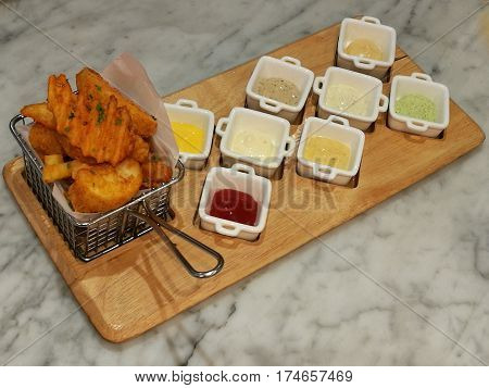 Golden French fries serving in the basket with 8 dipping sauces ketchup and mayo stylist food fusion food top view