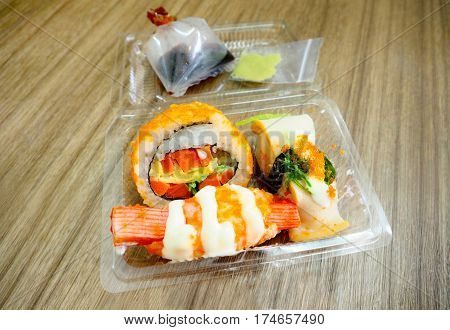 Sushi Japanese food in plastic box three pieces for retail sale in market kios shop Photo perspective macro focus select at center of sushi and zoom in .