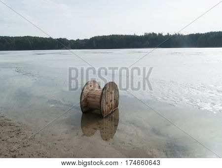 Wooden reel for electric cables in the water,spring landscape