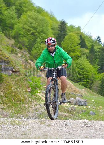 Romania Brasov County Transylvania May 05 2016 Remus Cucu athlete riding his bike on a trail in a spring day