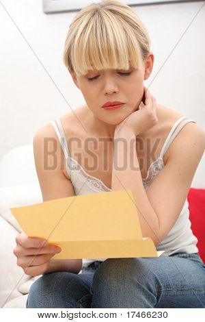 Worried woman's reading letter, at home.