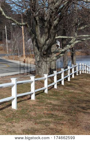 white post and beam fence leading to the water near a country road