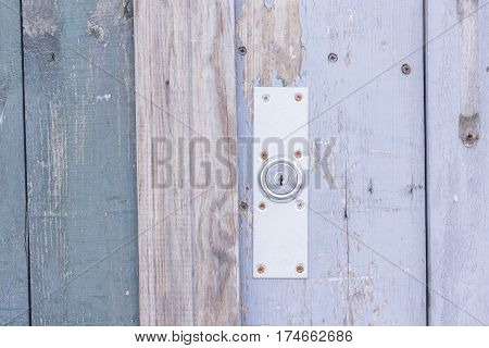 Old shabby wooden door with a lock on the street close up