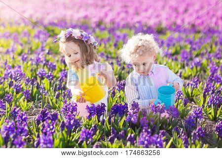Kids Plant And Water Flowers In Spring Garden