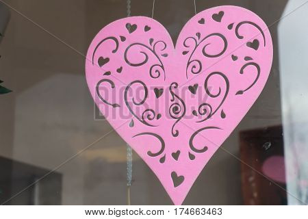 decorative pink felt heart hanging in a shop window