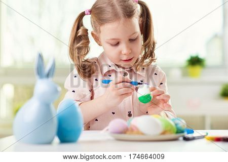 Happy Pretty Child Girl Having Fun During Painting Eggs For Easter In Spring
