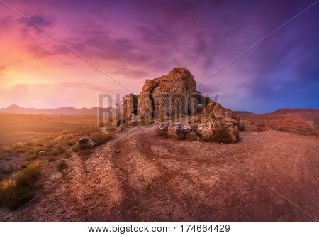 Desert With Lonely Rocks Against Multicolored Cloudy Sky