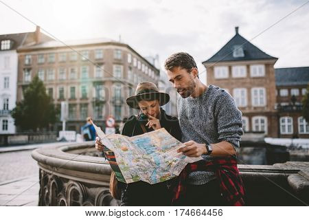 Young Tourist Couple Exploring A City Map.