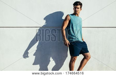 Shot of healthy young man standing against a wall outdoors. Fit young male relaxing after running exercise.