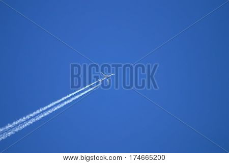 Jet plane pulling white contrails in clear blue sky. Airliner trail while transports passengers.