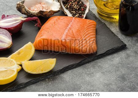 Ingredients for tar-tare sauce from a salmon rich in omega 3 oil with aromatic herbs and spices with a lemon tomato garlic on black background. Healthy and diet food.
