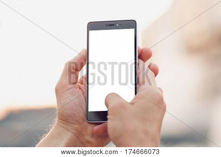 Making photo outdoors by smartphone. Hands holding and touch on blank smartphone with clipping path for screen.