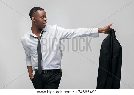 Businessman leaving office job. Going to the new level, next stage. African american guy on grey background.