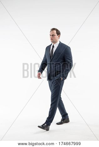 Portrait of walking businessman in a suit isolated on white background