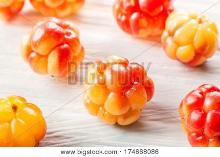 Berry cloudberries on light wooden background . close up. macro