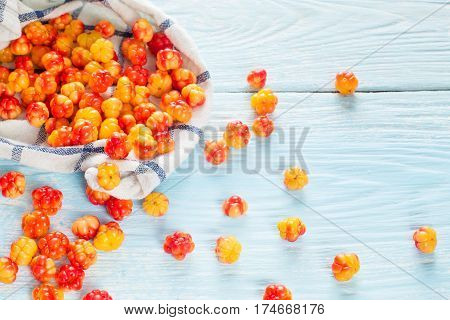 Berry cloudberries in the napkin on light wooden background.