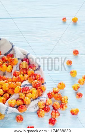 Berry cloudberries in the napkin on light wooden background. place for text