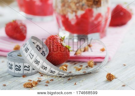 Dessert with fresh berries cottage cheese granola berries jam and measuring tape. Weight loss concept.