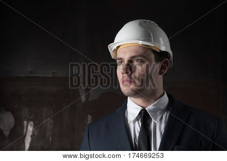 Portrait of a young architect in industrial concept in white helmet and in a stylish suit on dark background