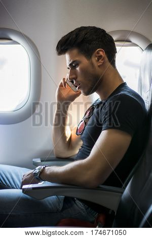 Side view of handsome young man against plane window sitting and talking on the phone