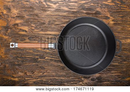 empty cast-iron frying pan on a wooden background