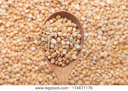 uncooked yellow peas in a wooden spoon on a background of spillage of dry peas