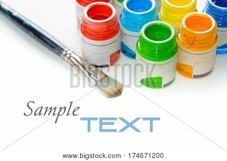 Jars with tempera paints and brush on white background with copy space. Selective focus with shallow depth of field